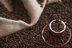 布朗咖啡杯和烤咖啡豆在木桌上与大袋在背景中 库存图片