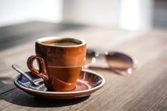 布朗咖啡杯,与玻璃的晴天 免版税库存图片