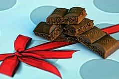 布朗在一张桌上的巧克力切片与一把红色弓 图库摄影