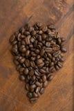 布朗在下落宏观咖啡豆形状,特写镜头背景的和纹理的咖啡豆 在棕色木板上 免版税库存图片