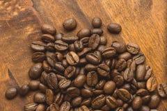 布朗在圈子的咖啡豆塑造,宏观咖啡豆特写镜头背景的和纹理 在棕色木板上 免版税库存图片