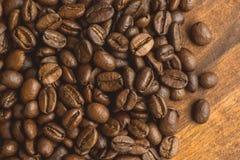 布朗在圈子的咖啡豆塑造,宏观咖啡豆特写镜头背景的和纹理 在棕色木板上 图库摄影