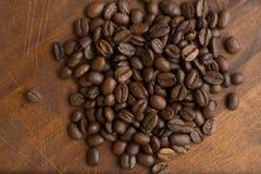 布朗在圈子的咖啡豆塑造,宏观咖啡豆特写镜头背景的和纹理 在棕色木板上 免版税库存照片