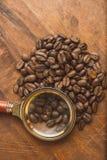 布朗在圈子的咖啡豆塑造,宏观咖啡豆特写镜头背景的和纹理 在棕色木板上与 免版税库存图片