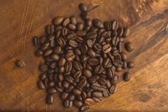 布朗在圈子的咖啡豆塑造,宏观咖啡豆特写镜头背景的和纹理 在棕色木板上与 库存图片