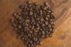 布朗在圈子的咖啡豆塑造,宏观咖啡豆特写镜头背景的和纹理 在棕色木板上 库存照片