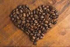 布朗在心脏、特写镜头背景的宏观咖啡豆和纹理形状的咖啡豆  在棕色木板上 库存图片