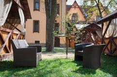 布朗在房子附近用皮革包盖沙发和两把椅子在庭院里 图库摄影