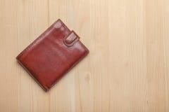 布朗在木桌上的皮革钱包 图库摄影