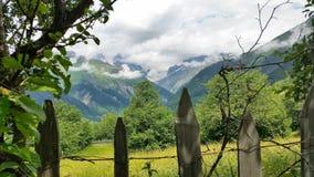 布朗在树和绿色山背景的村庄篱芭与多云天空,上部Svaneti,乔治亚 免版税图库摄影