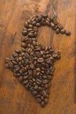 布朗在胡椒、特写镜头背景的宏观咖啡豆和纹理形状的咖啡豆  在棕色木板上 库存照片