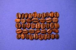 布朗在蓝色背景的咖啡豆 免版税库存照片