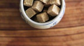 布朗在陶瓷碗的块糖在木切板 免版税库存图片