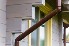 布朗塑料排水管设置了在房子角落 库存照片
