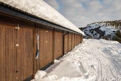 布朗多个车库大厦、雪在地面上,山和白色云彩在蓝天 免版税库存照片