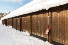 布朗多个车库大厦,与在墙壁上的一把红色在地面上的铁锹,雪和蓝天 库存图片