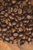 布朗宏观咖啡豆咖啡豆、特写镜头背景的和纹理 在棕色木板上 免版税库存图片