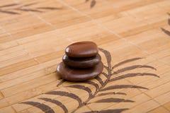 布朗按摩向在竹placemat的构成扔石头 免版税库存照片