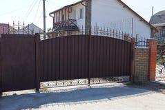 布朗有一个伪造的样式的金属门和一部分的在街道上的篱芭 免版税库存图片