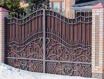 布朗有伪造样式和砖专栏的铁门在阳光下 免版税库存图片