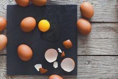 布朗有机破裂的鸡蛋用在黑木背景的卵黄质 免版税库存照片