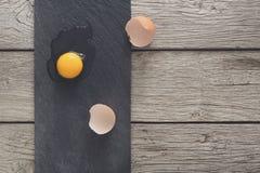 布朗有机破裂的鸡蛋用在黑木背景的卵黄质 免版税库存图片