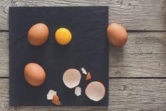 布朗有机破裂的鸡蛋用在黑木背景的卵黄质 库存照片