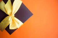 布朗有黄色丝带的礼物盒在橙色背景 与拷贝空间的顶视图 免版税库存照片