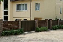 布朗木篱芭和门在草在路附近在一个大房子附近有窗口的 免版税库存照片