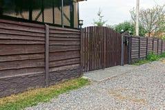 布朗木篱芭和闭合的门在街道上 免版税库存图片