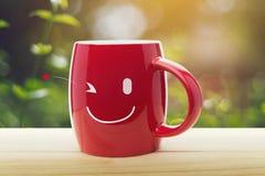 布朗杯子与愉快的微笑的咖啡 库存照片