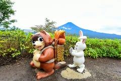 布朗浣熊和白色兔子雕象 免版税库存照片