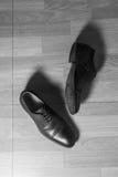 布朗用皮革包盖在木地面,失败概念,黑白过滤器的人鞋子 免版税库存照片
