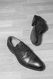 布朗用皮革包盖在木地面,失败概念,黑白过滤器的人鞋子 免版税库存图片
