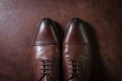 布朗用皮革包盖在皮革背景的人鞋子,在射击上 免版税图库摄影