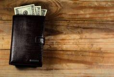 布朗用皮革包盖有美元的钱包在一张木桌上 库存照片