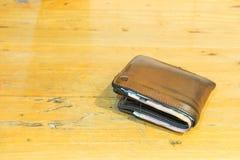 布朗用皮革包盖有钞票的人的钱包在棕色木纹理 免版税库存照片
