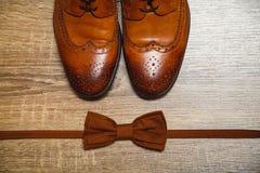 布朗男性鞋子和棕色蝶形领结 库存图片