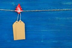 布朗白纸价牌或标号组和垂悬在蓝色背景的一条绳索的圣诞节木装饰 免版税库存照片