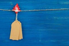 布朗白纸价牌或标号组和垂悬在蓝色背景的一条绳索的圣诞节木装饰 免版税库存图片