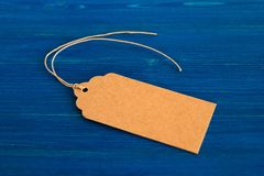 布朗白纸价牌或标号组在蓝色木背景 库存图片