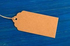 布朗白纸价牌或标号组在蓝色木背景 库存照片