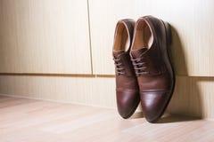 布朗皮革在木地面的人鞋子 库存图片