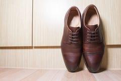 布朗皮革在木地面的人鞋子 免版税库存图片