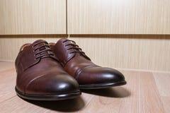 布朗皮革在木地面的人鞋子 免版税图库摄影