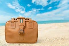 布朗皮革在海滩的葡萄酒手提箱 免版税图库摄影
