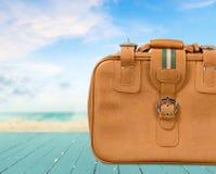 布朗皮革在海滩背景的葡萄酒手提箱 免版税库存图片