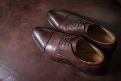 布朗皮革在皮革背景的人鞋子 免版税库存图片
