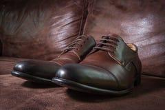 布朗皮革在皮革背景的人鞋子 免版税图库摄影