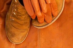 布朗皮鞋和手套在同样袋子背景  免版税库存图片